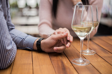Young couple holding hands at the cafe, closeup.