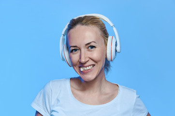 blonde with headphones listening to music and chewing gum on blue background
