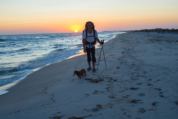 Traveler with a dog walks along the surf line