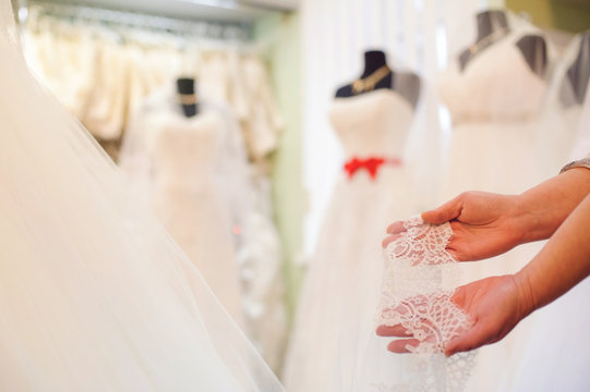 the consultant shows the lace on the background of the wedding dresses