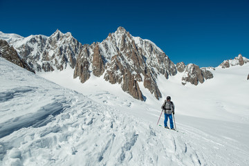 skier man exploring glacier or snowy land walking with snowshoes or alpine ski. Europe Alps Mont Blanc massif mount. Winter sunny day, snow. Wide long shot