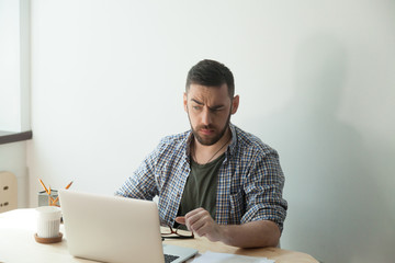 Fatigued male worker took off glasses and looking on screen of laptop. Manager with tired eyes feeling discomfort from long working behind notebook. Eyesight strain from computer work concept.