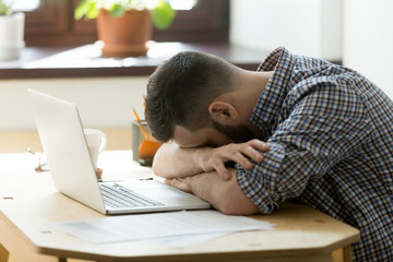 Tired manager falling asleep over laptop in hard working day in home office. Exhausted sleep deprived stressed male worker lying on table and sleeping after overwork, no energy left
