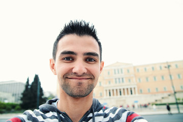 Man taking self portrait in the europe streets.Athens,Greece.Smiling young man.Travel selfie.Greek parlament.