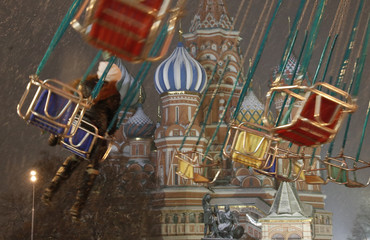 A visitor rides a merry-go-round in front of St. Basil's Cathedral in Red Square in Moscow