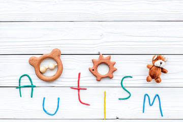 Childhood diseases. Word autism near toys on white wooden background top view copyspace