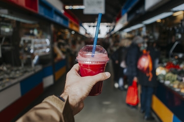 Hand holding a smoothie with red color. Traditional organics market in the background.