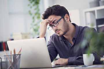 Young man working on computer and having headache