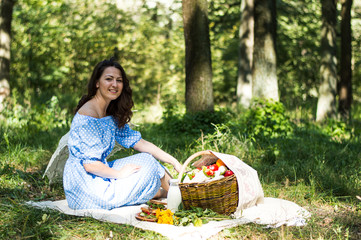 A young girl in a blue sarafan with an umbrella on a clearing in a forest at a picnic