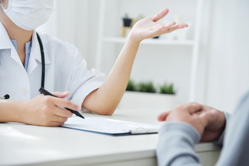 Asian Female Doctor discussing with patient.