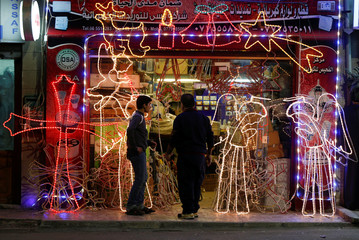 A Jordanian vendor displays Christmas lights at his shop in the town of Fuheis near Amman