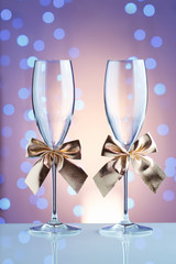 Festive champagne glasses with golden bows on a glass table with a beautiful blue bokeh