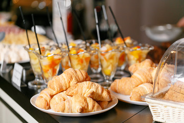Fresh pastry, crispy morning croissants, hotel breakfast buffet. Dessert fruit cocktail in cups