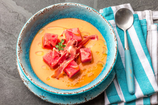 Salmorejo soup with watermelon. Traditional spanish cold tomato soup with watermelon and ham serrano in blue plate, slate background, top view