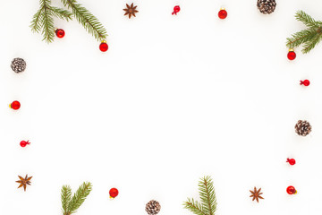 Christmas frame made of red christmas decorations, pine cone, anis stars, spruce branches on white background. Flat lay, top view, copy space