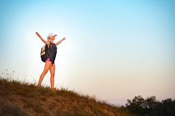 Successful girl backpacker, standing on the hill with open arms and enjoys the sunset