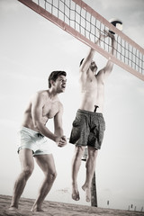 Two smilling male are playing in volleyball in time resting