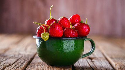 Fresh Strawberries in a Green enamel Cup on Vintage Wooden Background..Food or Healthy diet concept.Vegetarian.Copy space for Text. selective focus