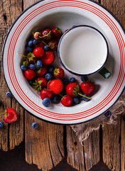 Fresh Strawberries and Blueberries  in the Iron bowl with a Cup of Milk on Vintage Wooden Background.Food or Healthy diet concept.Copy space for Text. selective focus.