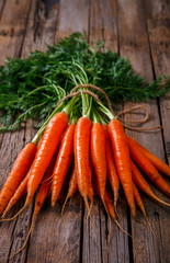 Bunch of fresh carrots with green leaves over wooden background. Vegetable.Food or Healthy diet concept.Vegetarian.Copy space for Text. selective focus.