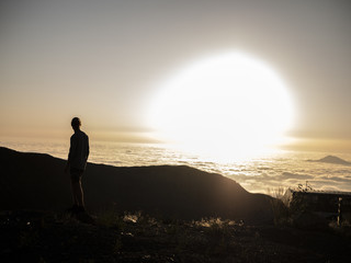 silhouette of man standing on the mountain above the clouds during sunset, huge sun