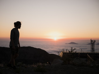silhouette of man standing on the mountain above the clouds during sunset