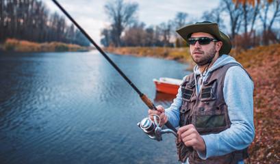 Spoed Fotobehang Vissen Angler enjoys in fishing on the river. Sport, recreation, lifestyle