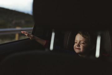 Cute boy with eyes closed enjoying road trip seen through vehicle seat