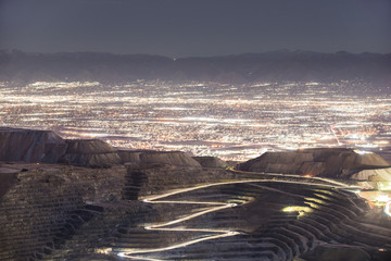 High angle view of Bingham Canyon against illuminated cityscape