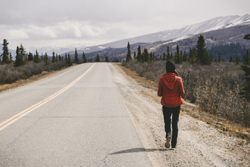Rear view of woman walking by country road at Denali National Park