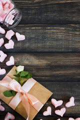 Marshmallow hearts, love letter and flowers on an old wooden background