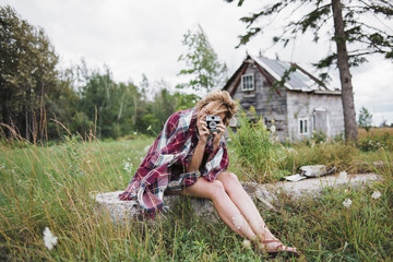 Woman photographing with instant camera while sitting on grassy field