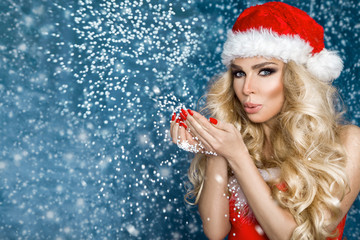 Beautiful sexy blonde female model dressed in a Santa Claus hat and sexy,red lingerie. Sensual girl for Christmas.