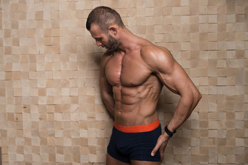 Model Flexing Muscles Against the Wall
