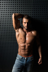 Portrait of Muscular Man Standing Near the Wall