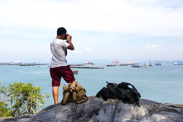 Unidentified photogragpher taking pictures of ocean with ship