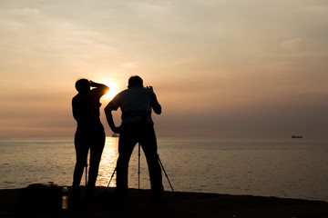 Silhouette of couple photographer taking photo of ocean at and sunset