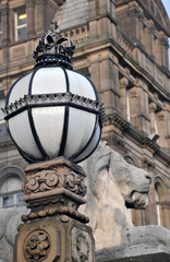 detail of lion sculpture and ornate lamp outside teeds town hall with city library in the background