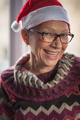 Senior old smiling woman wearing a christmas hat, looking forward to December holidays