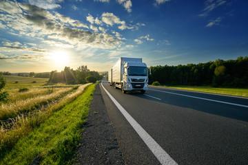Fotobehang - White delivery truck driving on the asphalt road in rural landscape at sunset
