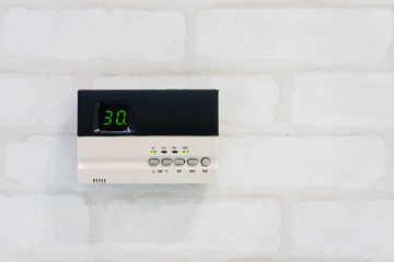 Modern programming thermostat in front of white brick wall with copyspace and text
