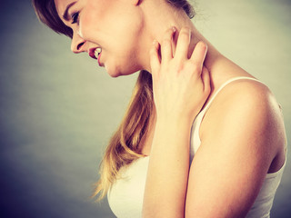 woman scratching her itchy neck with allergy rash