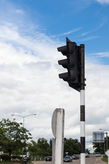 Traffic light pole with sky clouds.