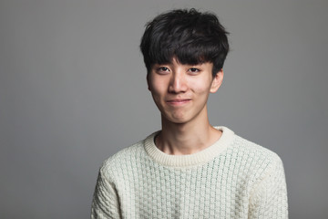 A studio portrait of an Asian man looking ahead with a confident smile Fotoväggar