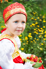 Beautiful little girl in russian costume with strawberry