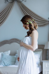 Young pregnant woman in white dress