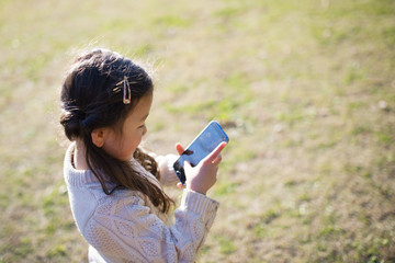 Little girl watching smartphone