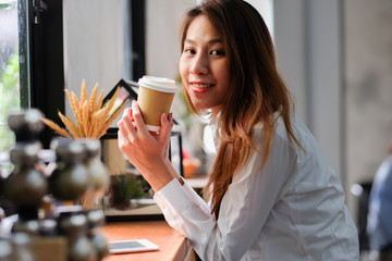 young beautiful asian woman drinking coffee with feeing relax and smiley face smart phone , sitting in loft coffee cafe.