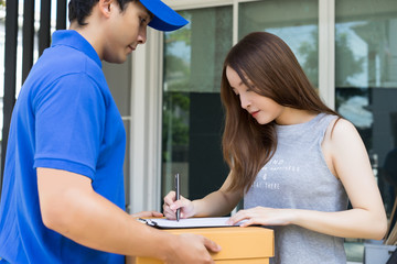 Friendly young delivery person in blue uniform holding cardboard box send to customer,Delivery concept, Service concept.
