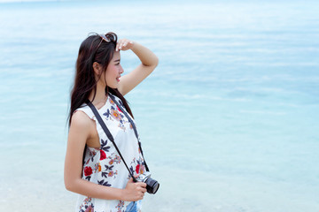 Asian woman taking photo with camera mirrorless at beach,Lifestyle hipster and travel relaxation,rest in summer season vacation concept